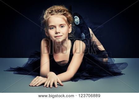 Cute little girl ballet dancer in black leotard and tutu posing in studio over black background.