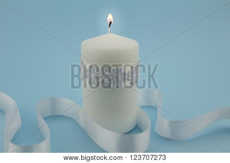Close up photo of single white lit candle isolated with white satin ribbon on blue background
