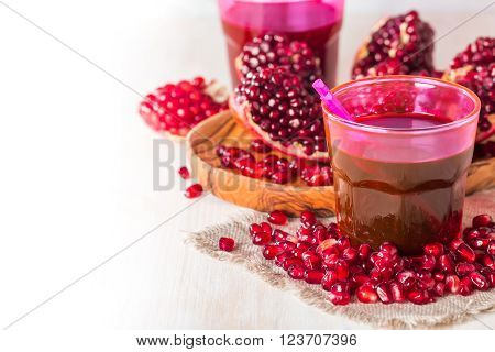 pomegranate juice and ripe red pomegranate fruit on white wooden table