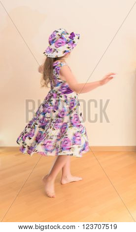 Little girl in dress twisting around blurred motion