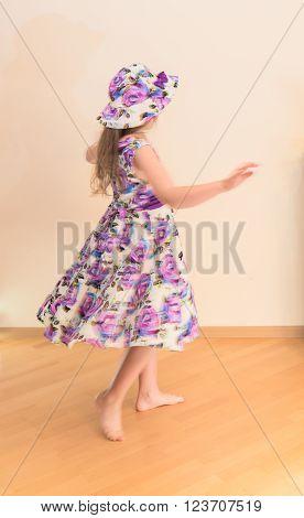 Little girl in dress twisting around blurred motion