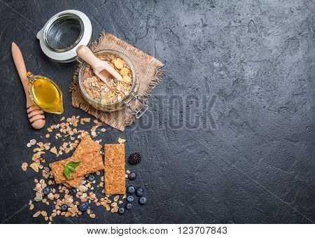 Granola bar from homemade granola with honey on black background, top view