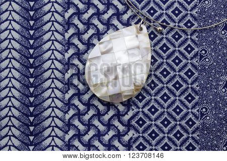 Close up photo of mother of pearl pendant necklace on blue and white printed cloth