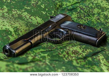 Weathered generic russian soviet semi-automatic 9mm pistol on pixel camouflage background