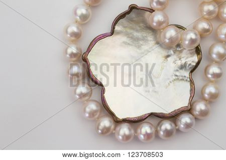 Top lay pale pink pearl necklace and mother of pearl pendant isolated on white