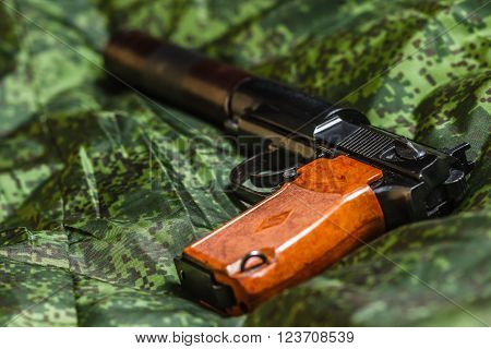 Weathered generic russian soviet semi-automatic 9mm silenced  pistol on pixel camouflage background