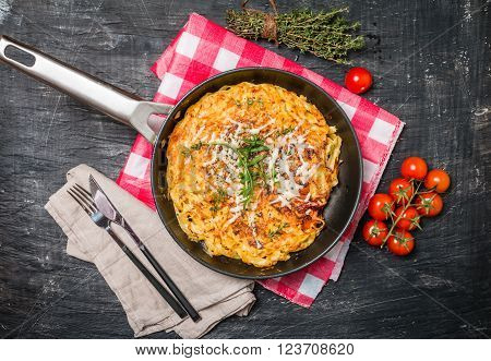 pasta casserole with eggs, sun-dried tomato and cheese in frying pan on black background, top view