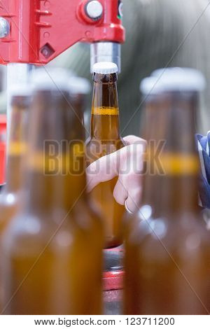 Unrecognizable man holding glass bottle. Beer bottles on foreground ** Note: Visible grain at 100%, best at smaller sizes