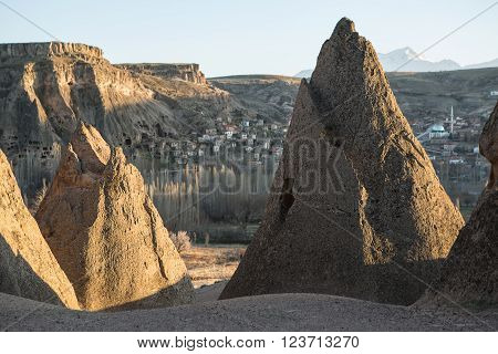 Rocks with houses carved into rock on the background of the old town in the valley and the sky. Sunlight touches the peaks of the rocks.