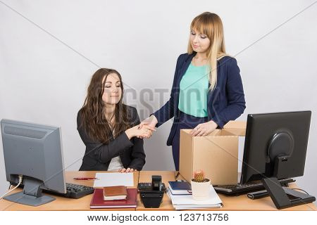 Girl In Office Standing With A Smile In Front Of The Box And Shakes Hands With A Colleague