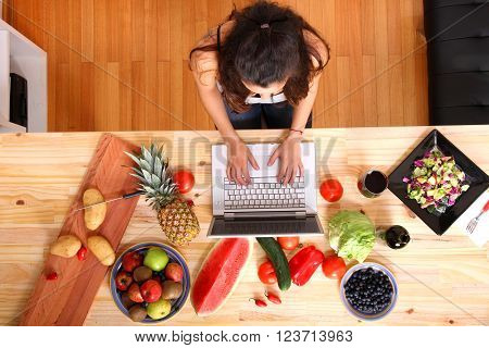 A young woman using a Laptop while cooking.
