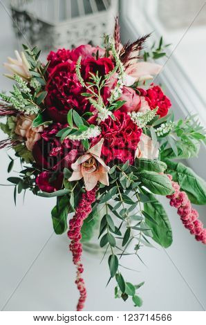 Wedding bouquet . The bride's bouquet. Bouquet of red and beige flowers, greenery, with a ribbon of color Marsala in vase on a white background
