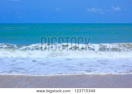 A tranquil sea scene. The waves crashing roll in and out are foamy. Beautiful seashells on beach, the water is a crystal-blue color. The sky above is a perfect blue color.