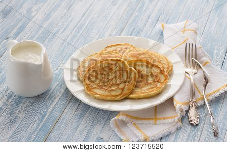 Freshly baked pancakes with sour cream on a textile tablecloths with sour cream on a light blue background