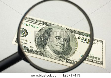 Hundred dollar bill and magnifying glass