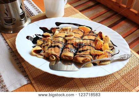 Pancakes stuffed with semolina, bananas and oranges drenched with dark chocolate