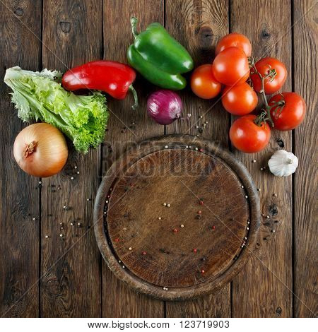 Various vegetables at wooden rustic background with copyspace on round pizza desk. Set of fresh vegetables. Vegetables top view, tomatoes, pepper, lettuce, onion, garlic, red onion. Pizza ingridients.