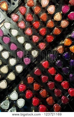 Set of different colors nail varnishes on shelves in cosmetic store