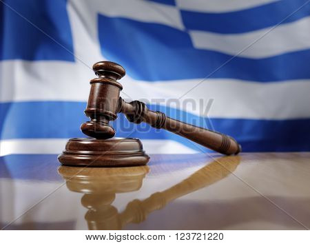 Mahogany wooden gavel on glossy wooden table, flag of Greece in the background.