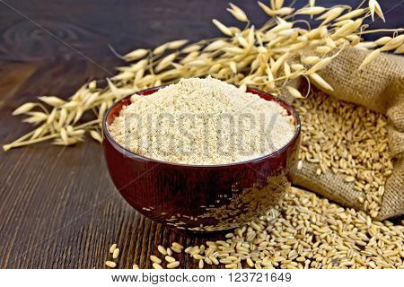 Oat flour in a bowl, bag with oat and stalks of oats on the background of dark wood planks
