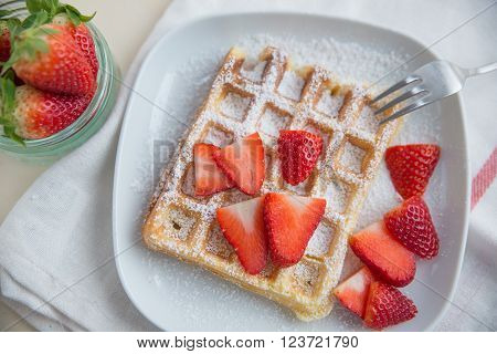 Home made waffles with fresh strawberries and sugar