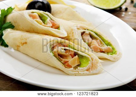 Restaurant food. Catering, buffet. Served dishes. Restaurant meals. Restaurant food - crepes rolls filled with salty salmon. Pancake, crepes rolls at wood. Served wooden table.