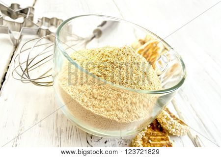 Sesame flour in a glass cupl with a mixer and molds for cookies, sesame seeds, cookies on a wooden boards background