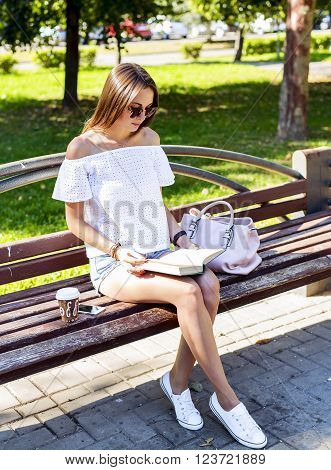 Young beautiful woman sitting in the park summer spring day, reading a book, with coffee, tea, phone bags, white sneakers, shorts and a white blouse, enjoy your holiday with a good book.