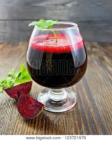 The juice of beet in wineglass, beet slices and parsley on a wooden board background