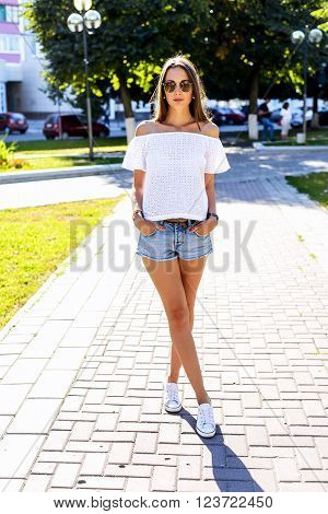 Beautiful young brunette girl in short denim shorts with glasses, fashion style urban life. Student in the park bright summer day outdoors. Resting after study. Posing on a street in the city.