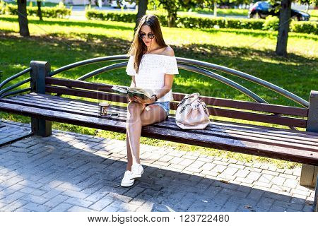Beautiful girl student with glasses and a bag of coffee, sitting on a park bench, reading a book, fashion style, school life, in the summer on a sunny day in the fresh air. Woman relaxing.