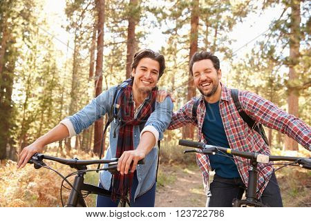 Portrait Of Gay Male Couple Cycling Through Fall Woodland
