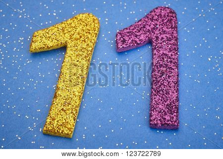 Number eleven yellow purple color over blue background. Anniversary. Horizontal