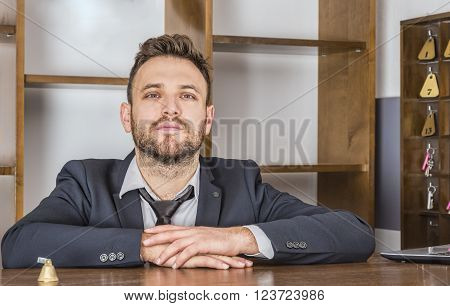 Portrait of a receptionist at his desk in a small hostel.