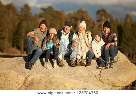 Multi generation family sitting on rocky outcrop near a forest