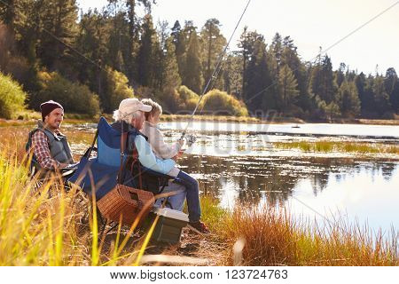 Grandad teaches his grandson to fish at a lake, dad watching
