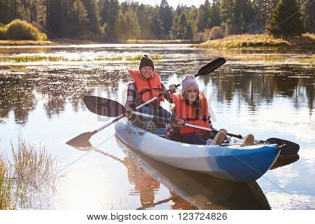 Mother and daughter kayaking on lake, front view, close-up