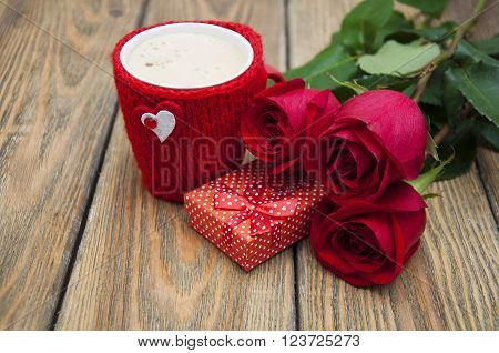A cup of cappuccino with heart gift box and red roses on a wooden background