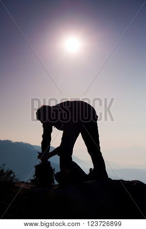 Professional photographer is packing camera into backpack on peak of rock. Dreamy fogy landscape, spring orange pink misty sunrise in a beautiful valley below