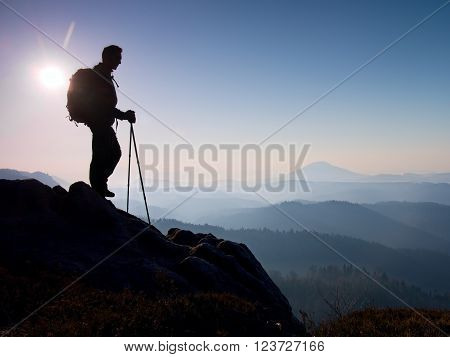 Tourist With Sporty Backpack And Poles In Hands Stand On Rocky View Point And Watching Into Morning