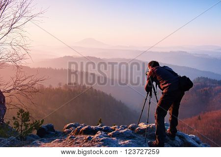 Professional photographer takes photos with camera on tripod on rocky peak. Dreamy fogy landscape, spring orange pink misty sunrise in a beautiful valley below
