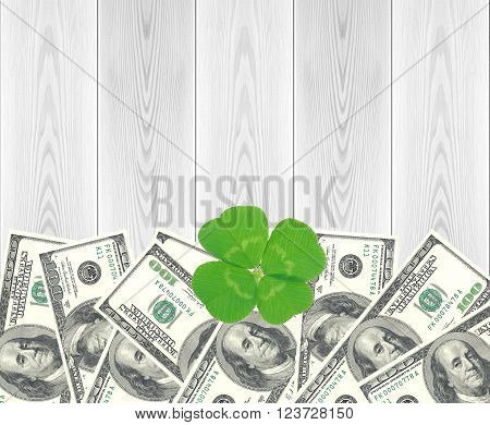 Clover leaf and dollars and white wooden table close-up