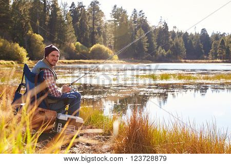 Man fishing by lakeside, looking to camera