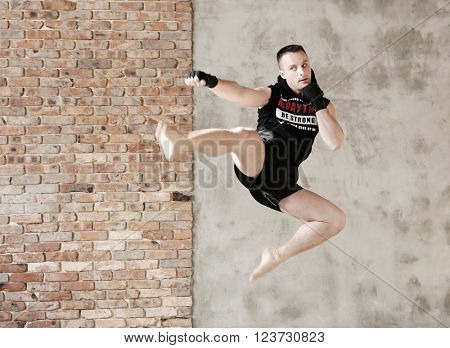 Sport. Handsome kickboxer in mid-air