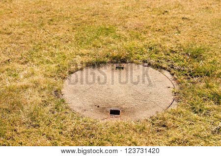 Concrete manhole cover drainage system in the midst of cropped grass