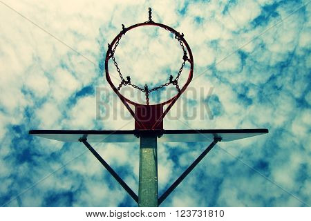 Old neglect basketball backboard with rusty hoop above street court. Blue cloudy sky in background.