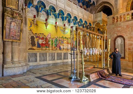 JERUSALEM, ISRAEL - JULY 26, 2015:  Stone of Anointing and mosaic icon on the wall at the entrance to Holy Sepulcher church designate the place where Jesus' body was prepared for burial.