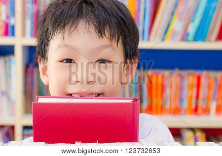 Young Schoolboy holding book and smiles in library