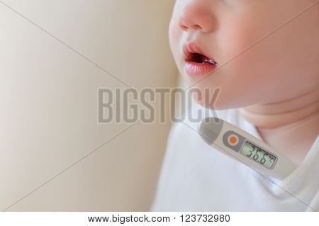 Sick and sad kid in bed holding thermometer