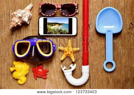 a rustic wooden table full of summer stuff, such a pair of sunglasses, a starfish, a conch, a diving mask or a snorkel, and a smartphone with the picture of a beach taken by myself in its screen